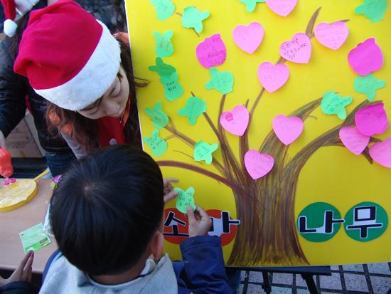 SK 자원봉사자와 함께 소망나무에 사진의 소망을 적어 꾸미는 아이